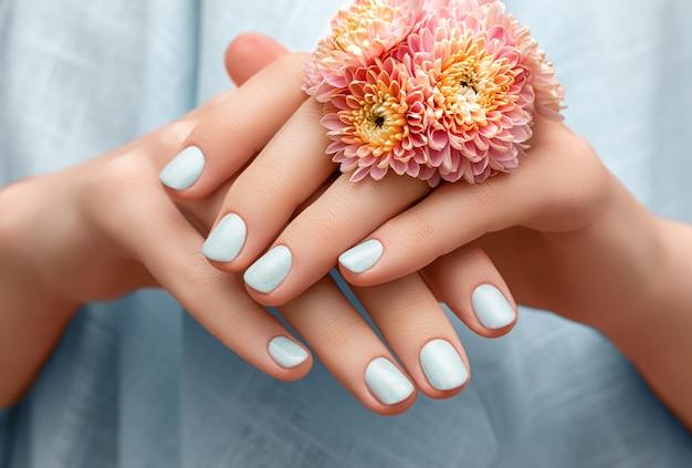 Vrouwelijke hand met blauw nageldesign met roze bloemenring.