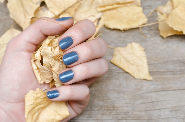 Vrouwelijke hand met blauw nagelontwerp