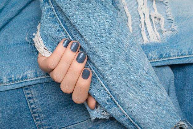 Vrouwelijke hand met blauw spijkerontwerp op het blauwe haveloze oppervlak van de denimstof.