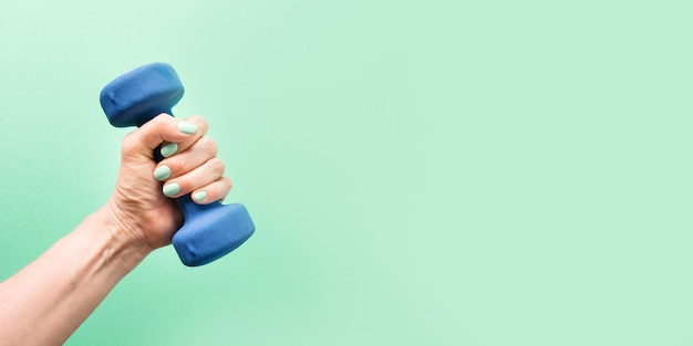 Vrouwelijke hand met blauwe halter op groene achtergrond sport fitness apparatuur