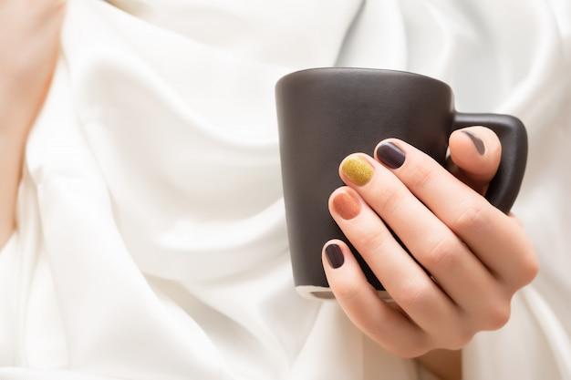 Vrouwelijke hand met bruin spijkerontwerp dat zwarte kop houdt.