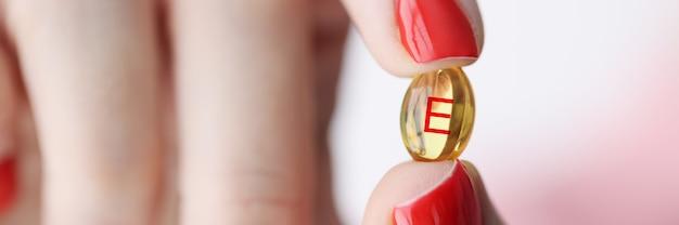 Vrouwelijke hand met capsule met vitamine e.
