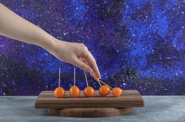 Vrouwelijke hand met cherrytomaat van houten bord.