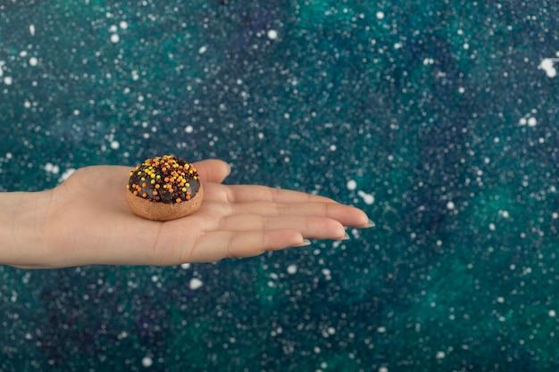 Vrouwelijke hand met cookie op kleurrijke oppervlak.