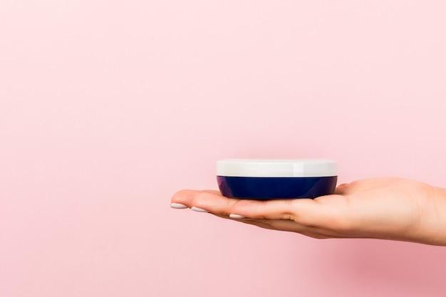 Vrouwelijke hand met cosmetica fles op roze achtergrond met lege ruimte voor uw ontwerp.