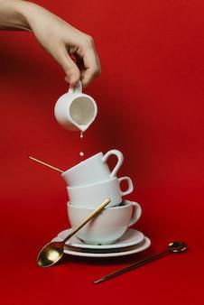 Vrouwelijke hand met creamer pot en gieten in stapel witte koffiekopjes