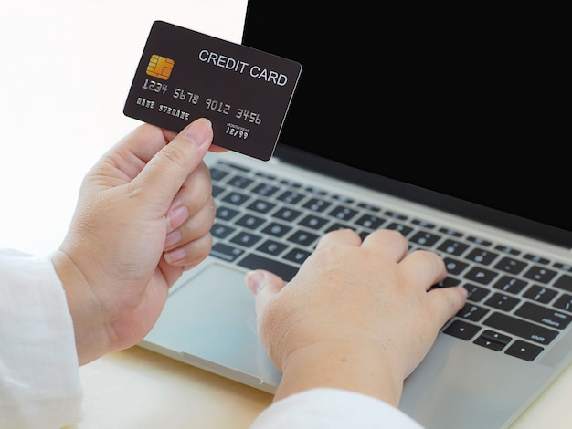 Vrouwelijke hand met creditcard en gebruiken om internet online factuur op computer, bankterminalrekeningconcept te controleren