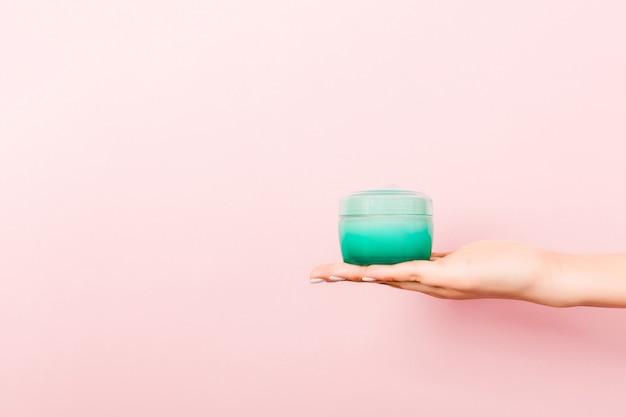 Vrouwelijke hand met crème fles lotion geïsoleerd. meisje geeft pot cosmetische producten op roze achtergrond.
