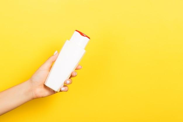 Vrouwelijke hand met crème fles lotion geïsoleerd