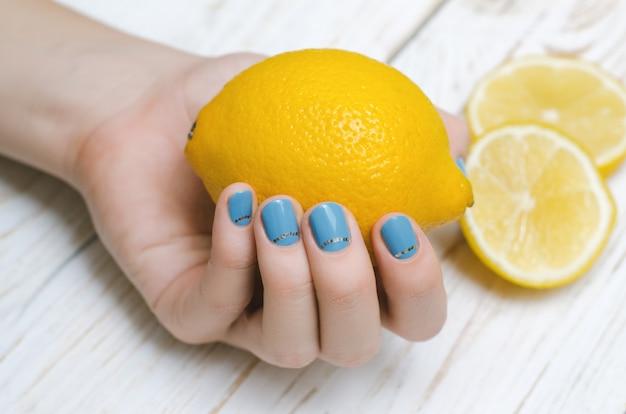 Vrouwelijke hand met de lichtblauwe citroen van de spijkerkunstholding.