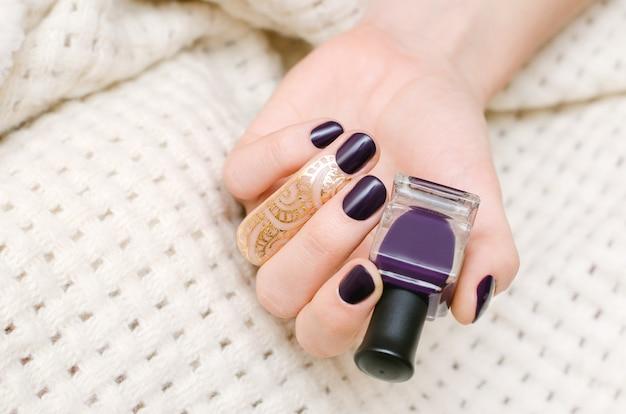 Vrouwelijke hand met donker paars nagelontwerp.