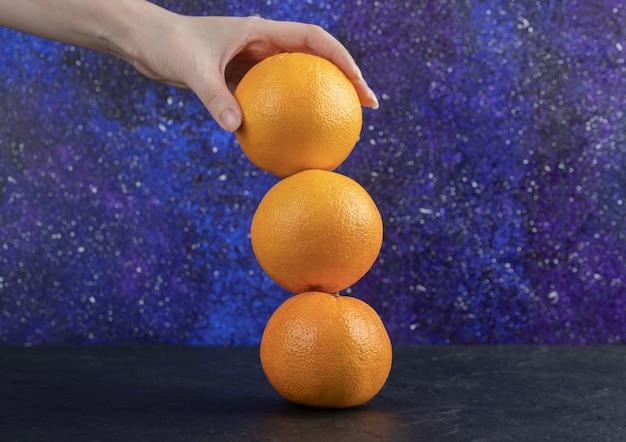 Vrouwelijke hand met drie sinaasappels op blauwe tafel.