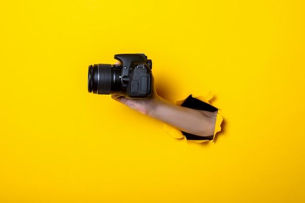 Vrouwelijke hand met een camera op een heldere gele achtergrond