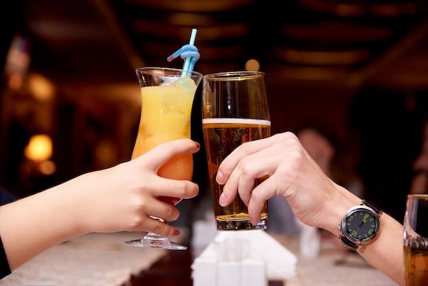Vrouwelijke hand met een cocktail en een mannelijke hand met bierclose-up.