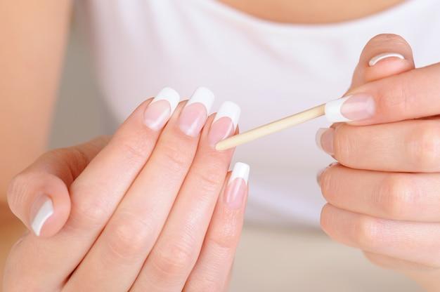 Vrouwelijke hand met een cosmetische stok voor het reinigen van de nagelriem