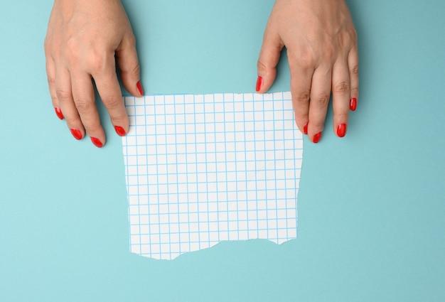 Vrouwelijke hand met een gescheurd blanco vel papier in een kooi op een blauwe achtergrond
