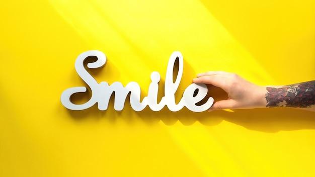 Vrouwelijke hand met een glimlach-titel op de gele achtergrond