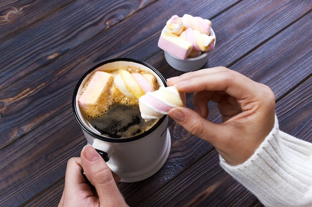 Vrouwelijke hand met een kop warme koffie met marshmallow