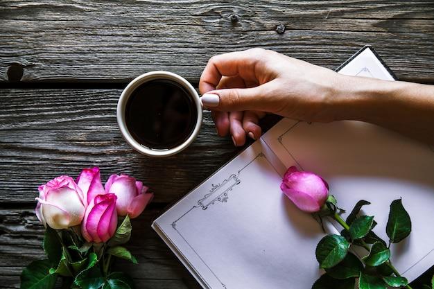 Vrouwelijke hand met een kopje koffie, een boek en bloemen op houten achtergrond. bloemen, breken, werken