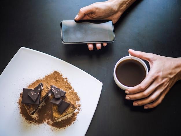 Vrouwelijke hand met een kopje koffie, een telefoon en een mooie close-up van de chocoladetaart op tafel