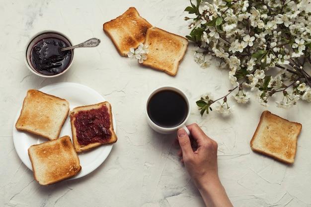Vrouwelijke hand met een kopje koffie, jam, toast, lente takken boom met bloemen. ontbijt concept. plat lag, bovenaanzicht
