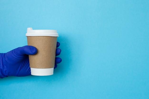 Vrouwelijke hand met een kopje koffie kopje. kopieer ruimte. koffiekop ter beschikking met medische handschoenen die op blauwe achtergrond worden geïsoleerd. hand met papieren beker, coronavirusbescherming