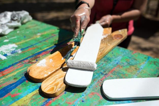 Vrouwelijke hand met een kussen schildert een houten bord