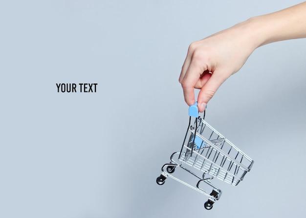 Vrouwelijke hand met een mini-winkelwagentje op een grijze achtergrond. kopieer de ruimte winkelen concept