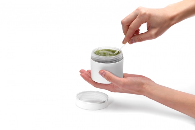Vrouwelijke hand met een natuurlijke vegan groene crème