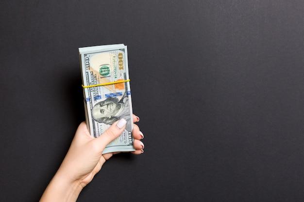 Vrouwelijke hand met een pak van honderd dollar