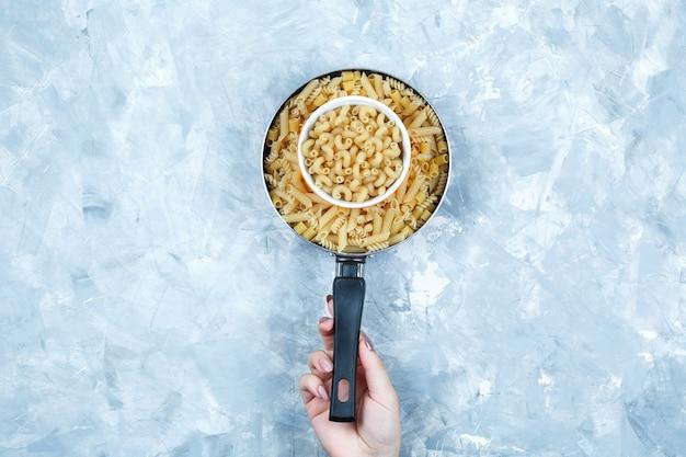 Vrouwelijke hand met een pan rauwe pasta, vooraanzicht.