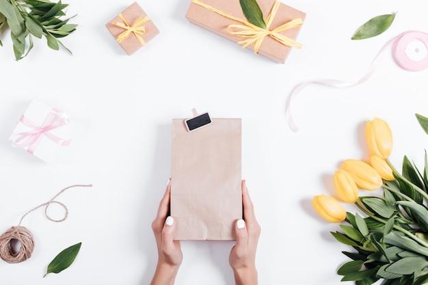 Vrouwelijke hand met een papieren zak met een geschenk op een tafel in de buurt van de tulpen, linten en vakken