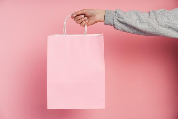 Vrouwelijke hand met een roze papieren zak geïsoleerd.