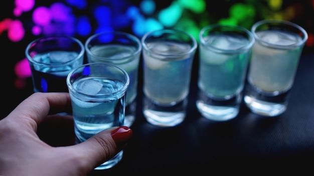 Vrouwelijke hand met een schot van alcohol, neon wazige achtergrond in bar