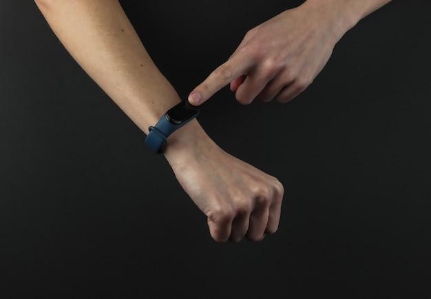 Vrouwelijke hand met een slimme armband op een zwarte achtergrond. moderne gadgets