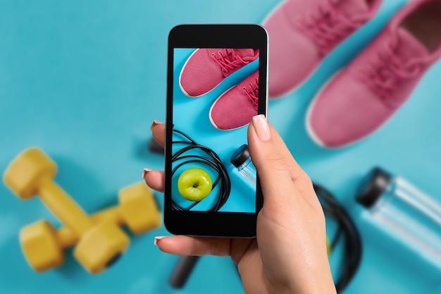 Vrouwelijke hand met een smartphone maakt een foto fitnessapparatuur op blauwe achtergrond