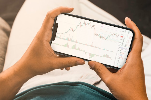 Vrouwelijke hand met een smartphone met financiële beursgrafiek op het scherm. beurs. rio de janeiro, rj, brazilië. september 2021.