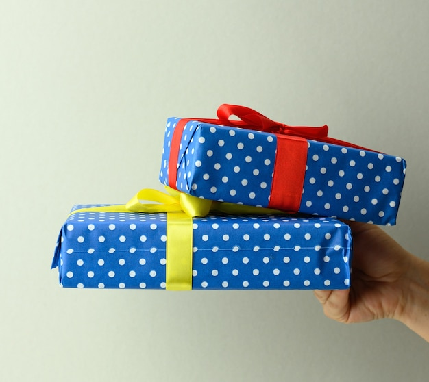 Vrouwelijke hand met een stapel geschenkdozen vastgebonden met zijden lint op een grijze achtergrond, verrassing en win