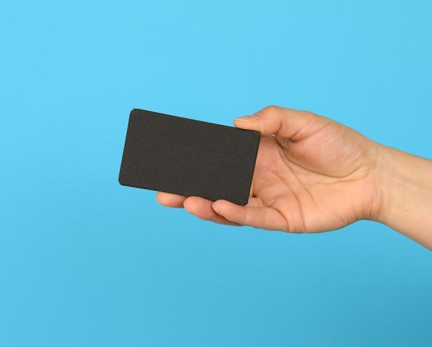 Vrouwelijke hand met een stapel lege zwarte visitekaartjes