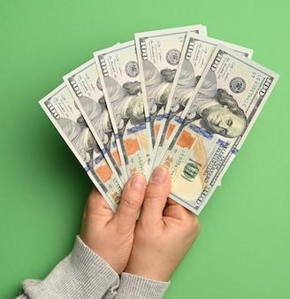 Vrouwelijke hand met een stapel papier honderd-dollarbiljetten op een groene achtergrond