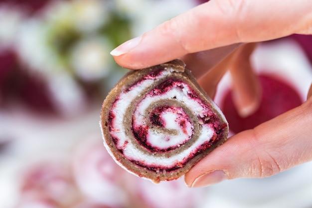 Vrouwelijke hand met een veganistisch frambozenbroodje