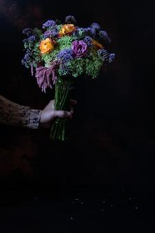 Vrouwelijke hand met een vintage boeket van prachtige herfstbloemen