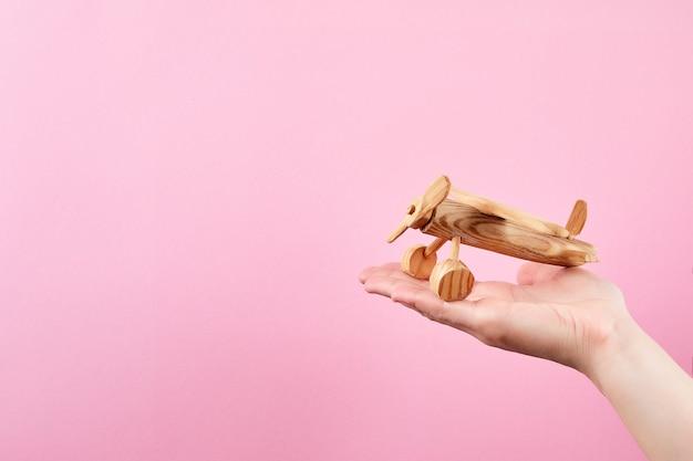 Vrouwelijke hand met een vliegtuig op een pastel roze achtergrond. handgemaakt houten vliegtuig.