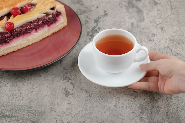 Vrouwelijke hand met een witte kop hete thee in de buurt van lekkere cake op een stenen tafel.