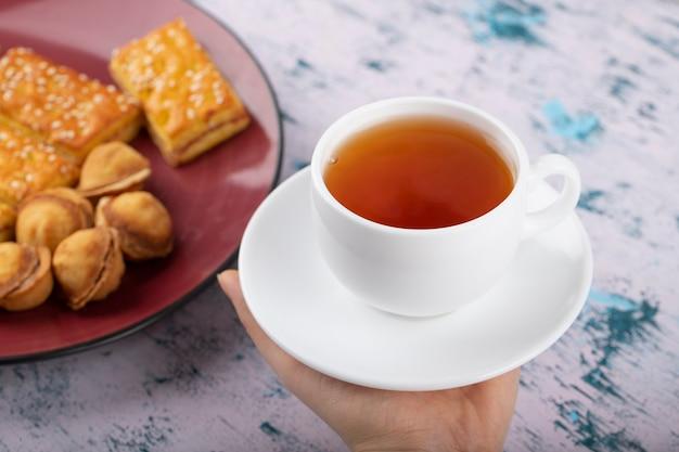 Vrouwelijke hand met een witte kop thee in de buurt van plaat met zoete koekjes.