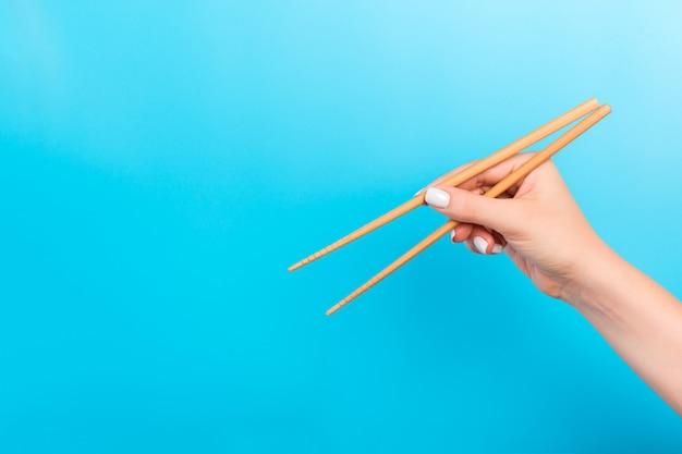 Vrouwelijke hand met eetstokjes op blauwe achtergrond. traditioneel aziatisch eten