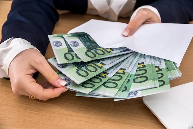 Vrouwelijke hand met envelop met euro geld. geld concept