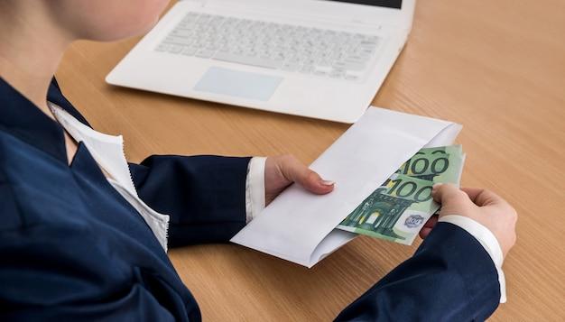 Vrouwelijke hand met envelop met euro geld