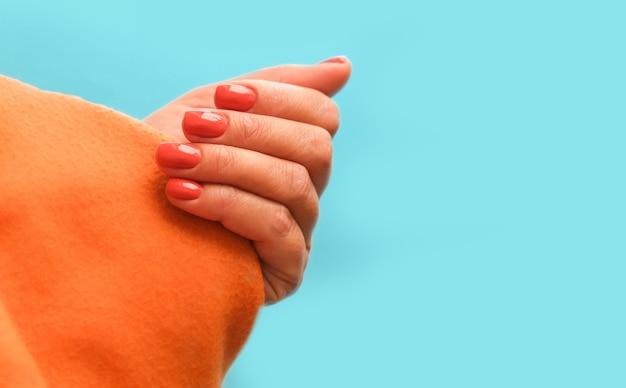Vrouwelijke hand met feloranje manicure op kleurrijke oranje en blauwe achtergrond helder zomerconcept copyspace voor tekst