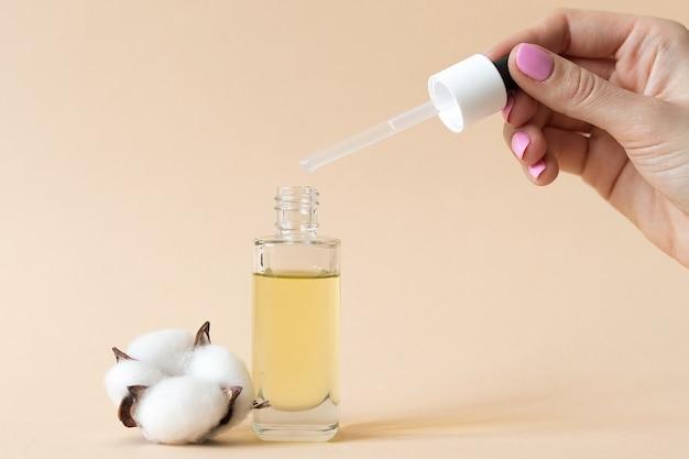 Vrouwelijke hand met fles met cosmetische arganolie, huidverzorging concept. hoge kwaliteit foto